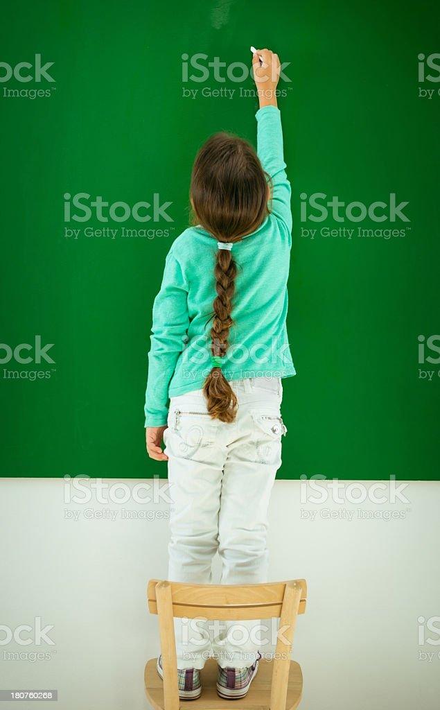 Preschooler standing in front of blank blackboard stock photo