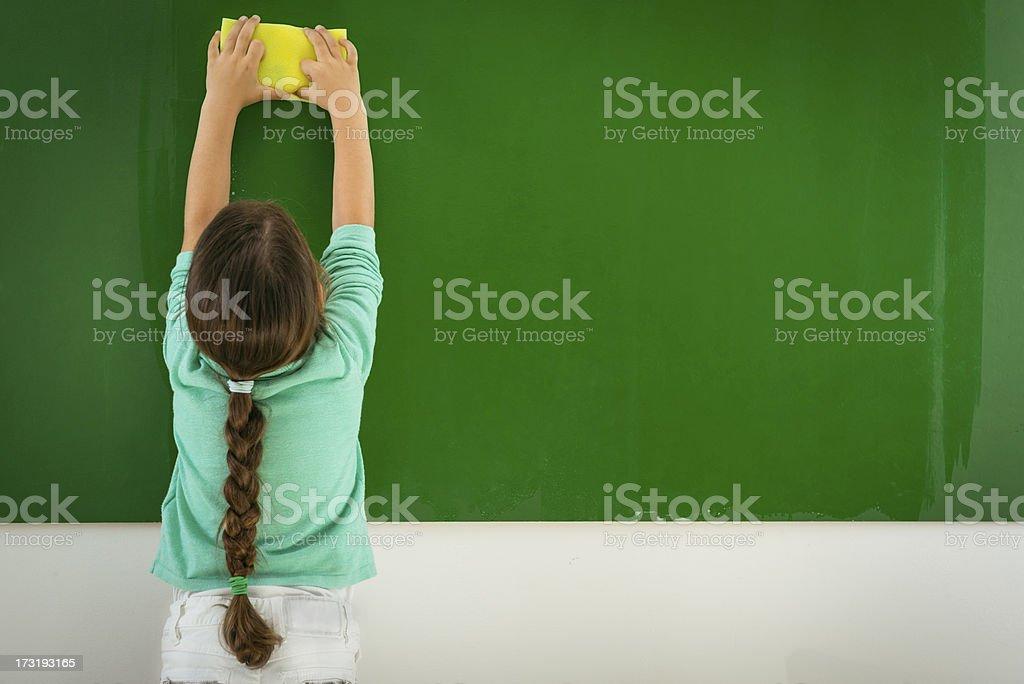 Preschooler wiping a blackboard stock photo