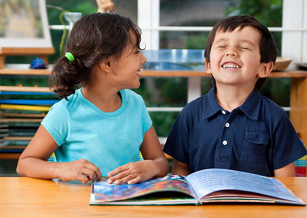 Preschoolers enjoying a book stock photo
