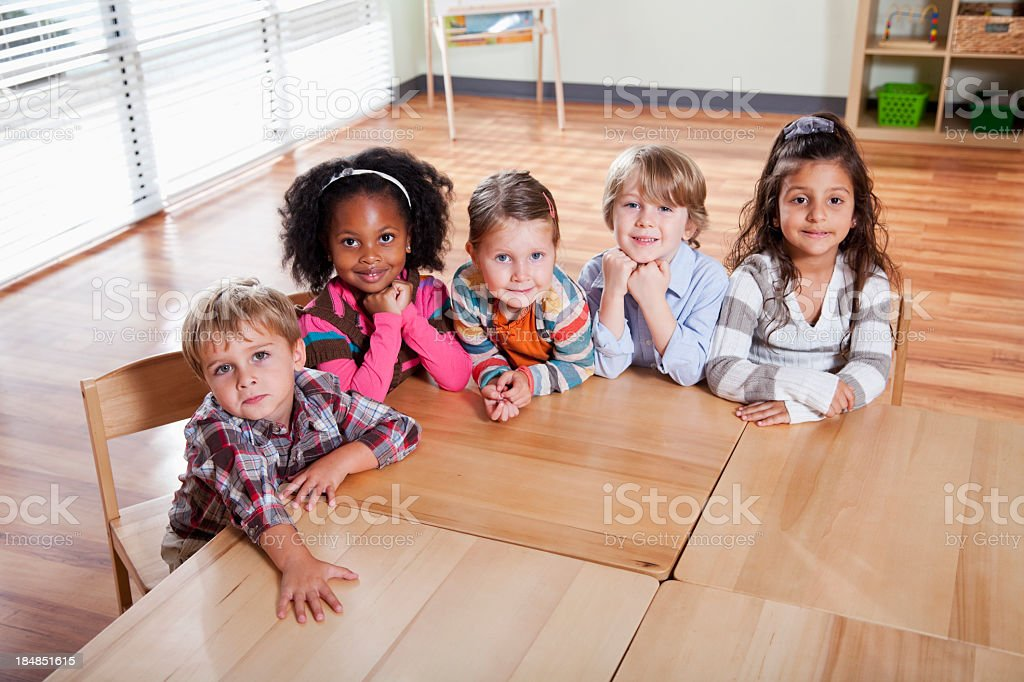Preschoolers sitting at table in classroom royalty-free stock photo