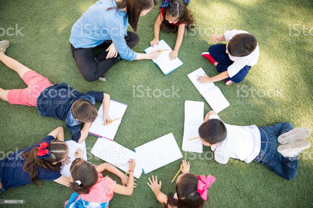 Preschoolers taking a class outdoors stock photo