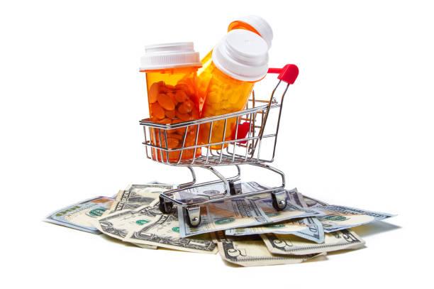 Prescription drug bottles in shopping cart on dollar bills stock photo