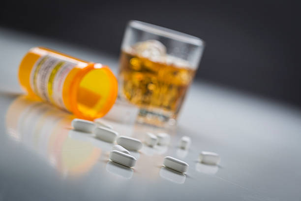 prescription drugs spilled from fallen bottle near glass of alcohol - alcohol stock photos and pictures