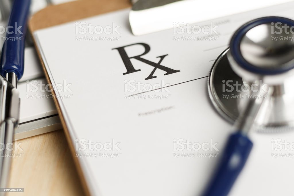Prescription form clipped to pad lying on table stock photo