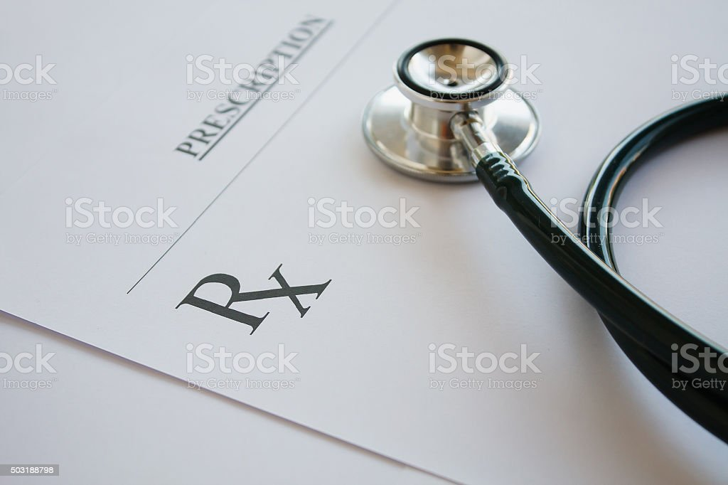 Prescription form lying on table with stethoscope stock photo