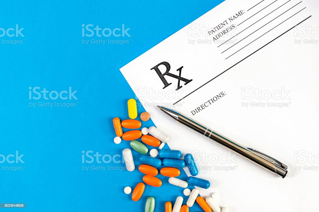 Prescription form with pills and pen with on blue. Top view. Medical concept. stock photo