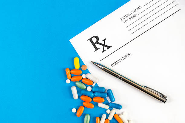 prescription form with pills and pen with on blue. top view. medical concept. - prescription medicine stock pictures, royalty-free photos & images