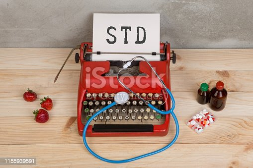 istock Prescription medicine or medical diagnosis - doctor workplace with stethoscope, pills, typewriter with text STD Sexually Transmitted Diseases, strawberries 1155939591