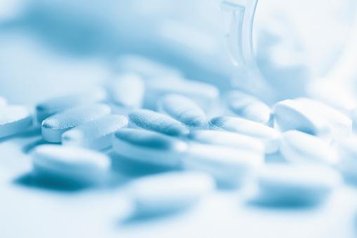 Prescription medicine pill bottle and pills.