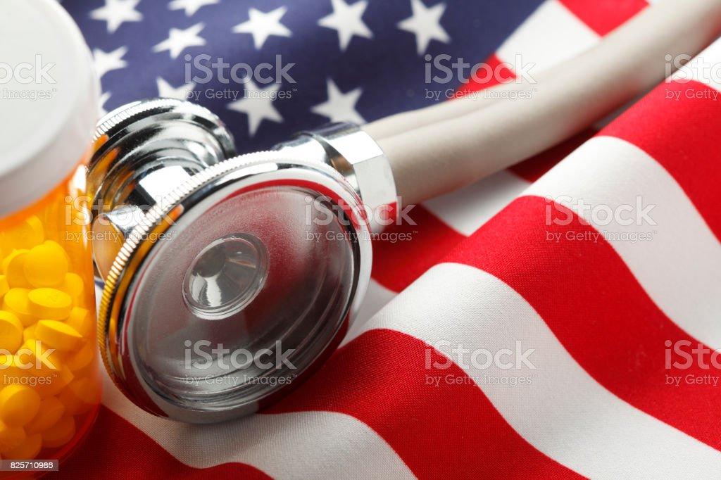 Um frasco de comprimidos de receita médica e estetoscópio sobre um americano Fla - foto de acervo