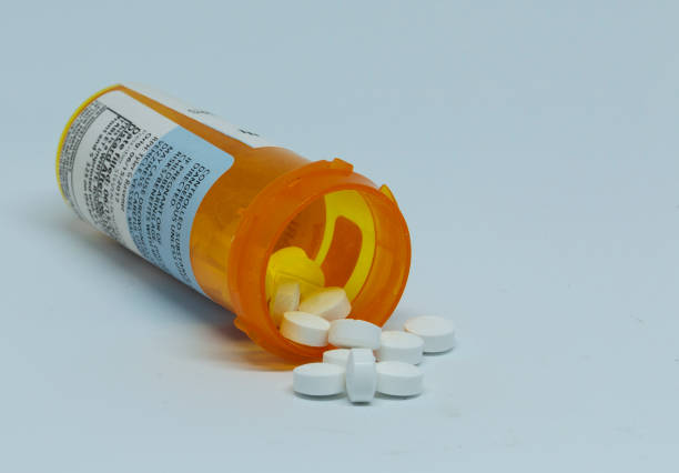 Prescription Pill bottle with pills spilling out Perscription pain pills are spilling out of the plastic pill container which is laying on its side. opioid stock pictures, royalty-free photos & images