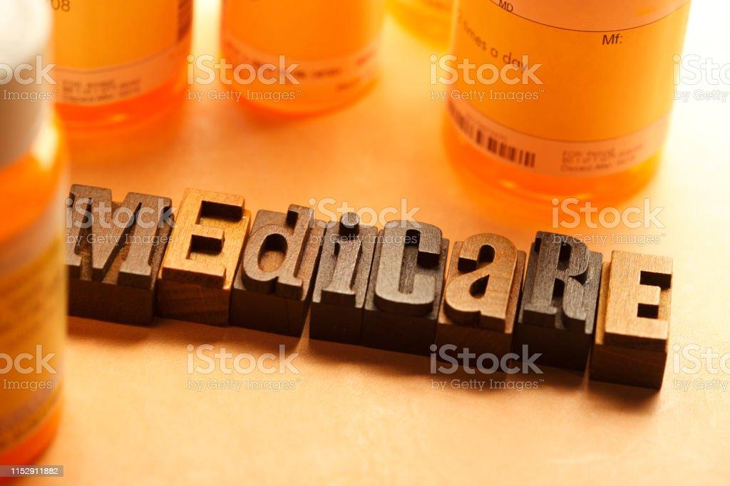 Prescription pill bottles surround letterpress letters that spell out...