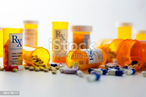 Prescription bottles and pills on a counter.