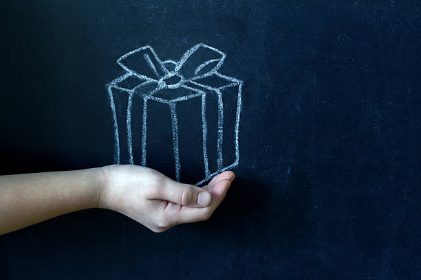 present and child's hand abstract background - teachers day stock photos and pictures