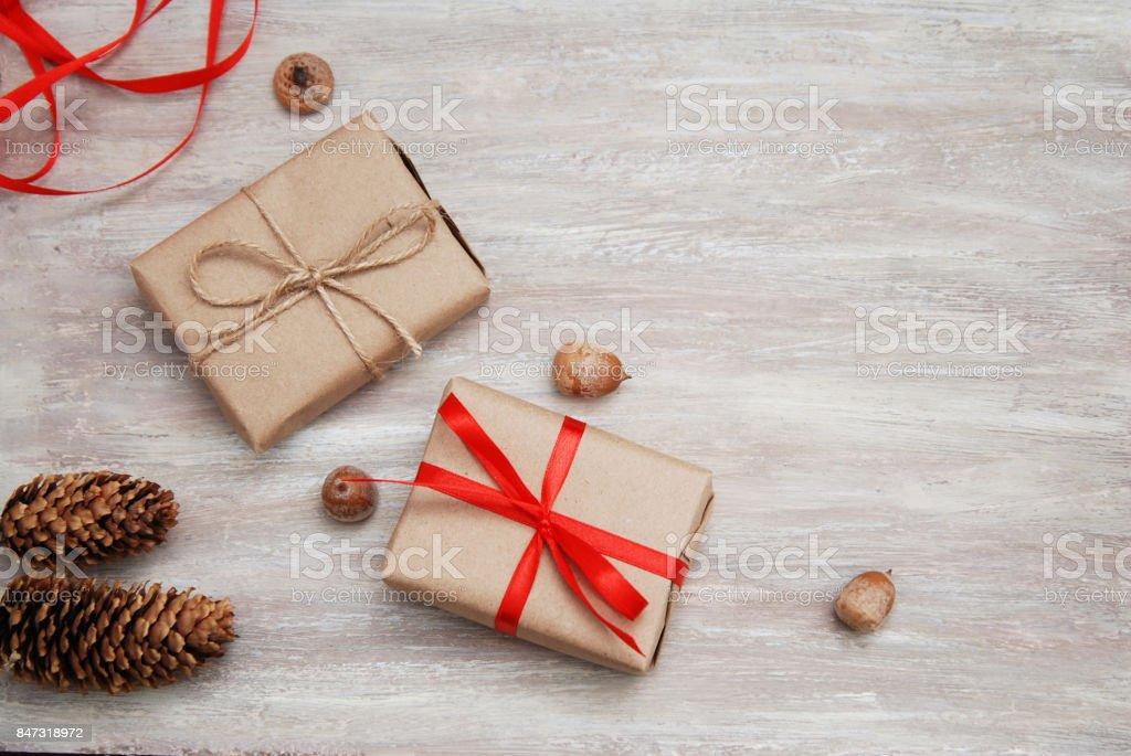 Present box from brown papaer with red ribbon bow on rustic background stock photo
