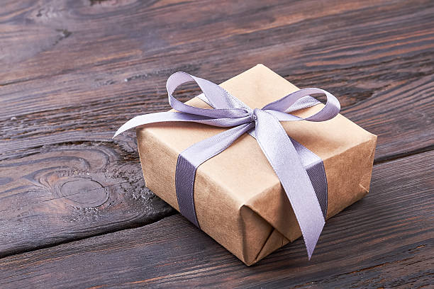present box on wooden surface. - birthday gift stock photos and pictures