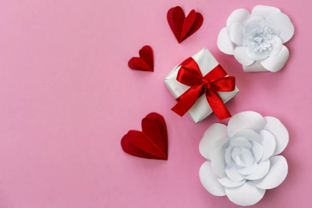 Present box with red ribbon, hand crafted paper hearts and flowers, copy space on left. stock photo