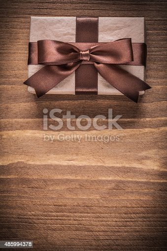 Present container with brown bow on vintage wooden board copyspace.