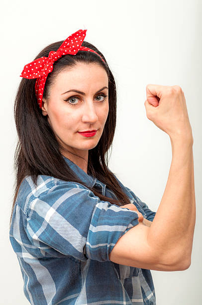 """Present day Rosie the Riveter Modern spin on Rosie the Riveter, a cultural icon of the United States, representing the American women who worked in factories and shipyards during World War II in the """"We can do it !"""" campaign, she is commonly used as a symbol of feminism, women's economic power and equality between sexes in the workforce. war effort stock pictures, royalty-free photos & images"""