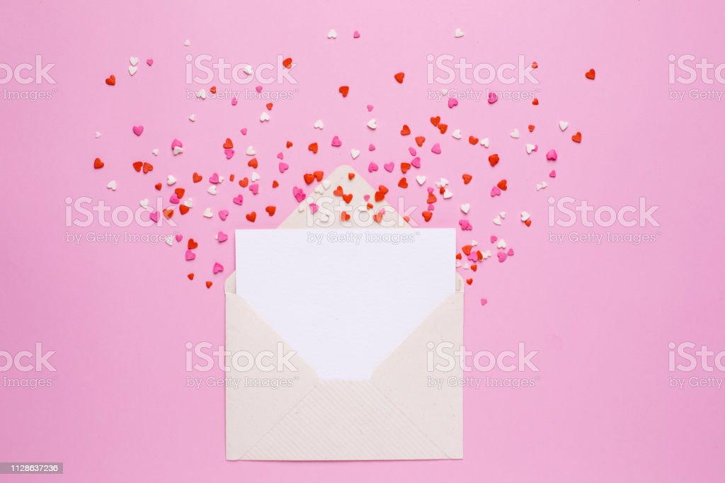 Present envelope and card with pink and red hearts on pink background...