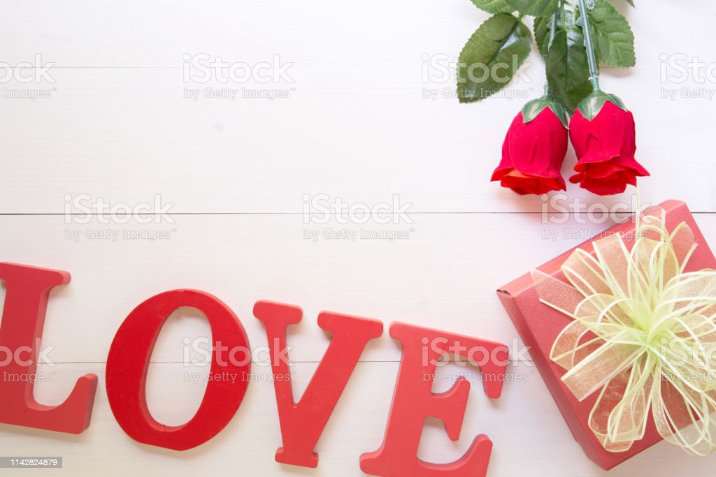 Present gift with red rose flower and gift box with bow ribbon on...