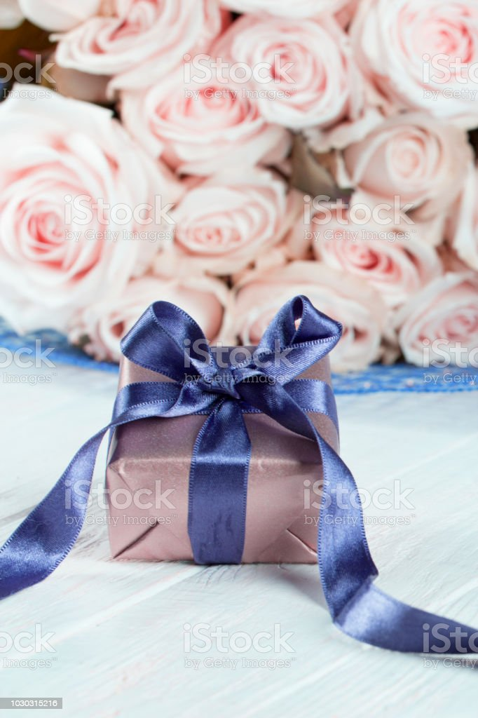 present gifts box. rose flowers and gift box with ribbon on light...