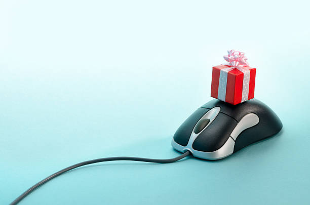 a present laying on a computer mouse - anniversary stock photos and pictures