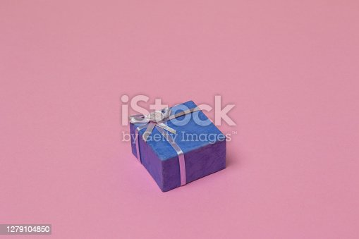 flat lay of a purple wrapped present on a pink background