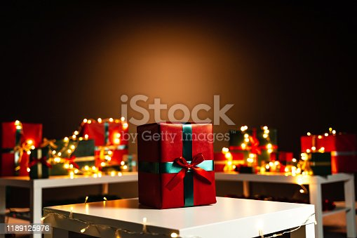 507751629 istock photo Present on white table, defocused Christmas lights in background, bokeh 1189125976