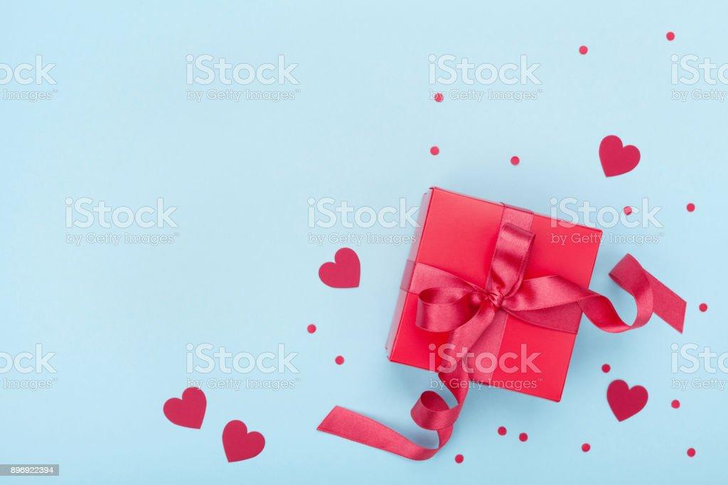 Vista presente ou caixa de presente, coração de papel e confete em cima de fundo azul. Cartão de dia dos namorados. - foto de acervo