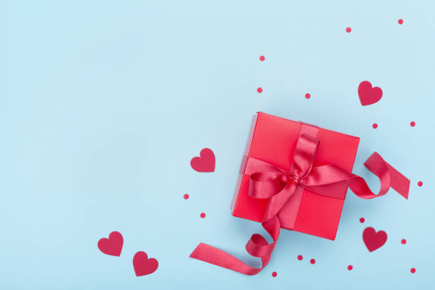present or gift box, paper heart and confetti on blue background top view. valentines day greeting card. - february stock photos and pictures