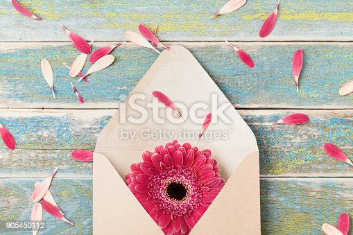680461500istockphoto Present or gift message concept with single gerbera flower in kraft envelope. Greeting card on mother or woman day. 905450112
