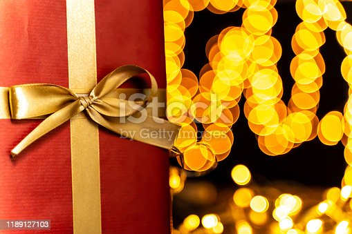 507751629 istock photo Present ribbon close-up, defocused Christmas lights, bokeh 1189127103