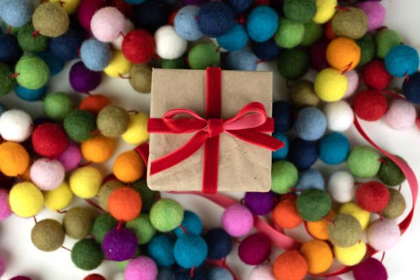 geschenk mit schleife gegen bunte girlande gebunden. - filz kugel girlande stock-fotos und bilder