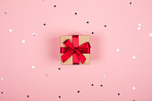 Present with red bow on pink background