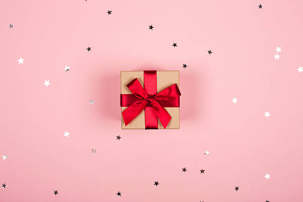Present with red bow on pink background stock photo
