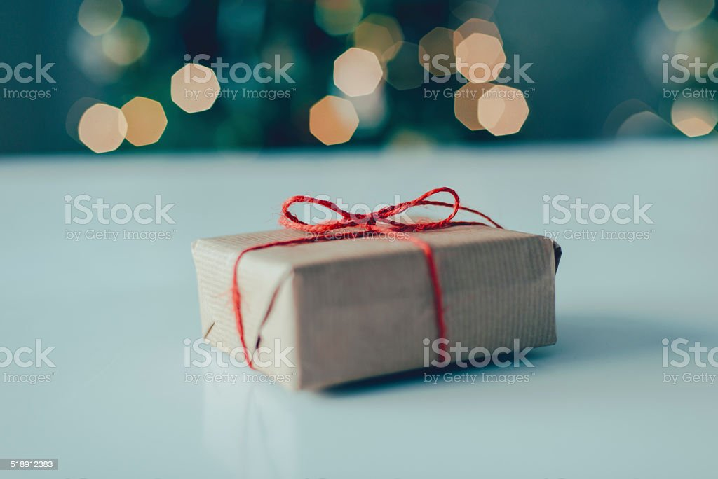 Present wrapped in brown paper Red ribbon around a gift with brown wrapping paper. Birthday Stock Photo