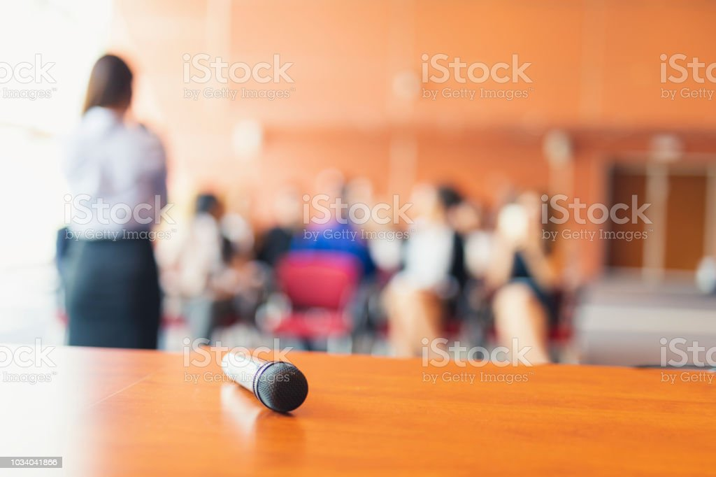 A business presentation in the board room, focus on the microphone