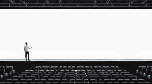 präsentation-halle mit person auf szene auditorium leerer bildschirm mockup - stage stock-fotos und bilder
