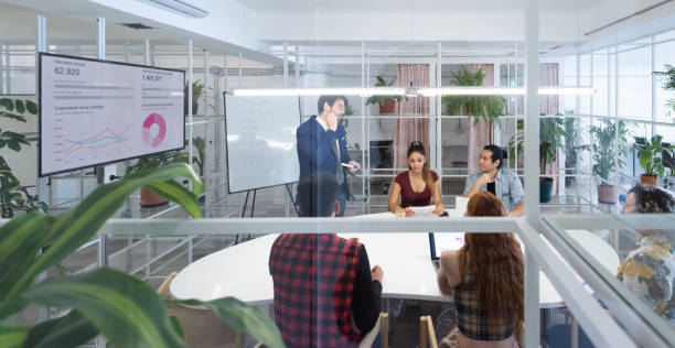 Presentation in multi ethnic business team meeting, seen from outside through windows stock photo
