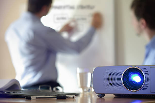 Presentation with lcd projector Business conference or lecture with businessman writing on whiteboard and lcd projector in foreground overhead projector stock pictures, royalty-free photos & images