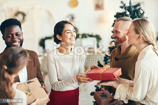 Group of elegant young people exchanging gifts and smiling cheerfully during Christmas party, copy space
