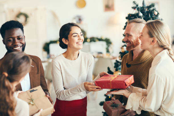 Presenting Christmas Gifts Group of elegant young people exchanging gifts and smiling cheerfully during Christmas party, copy space gifts stock pictures, royalty-free photos & images
