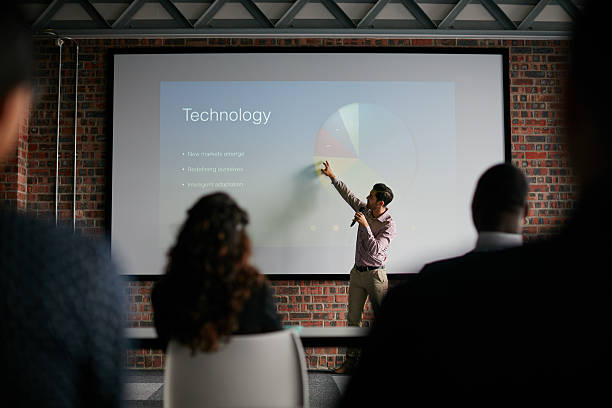 presenting key notes to his colleagues - projection screen stock photos and pictures