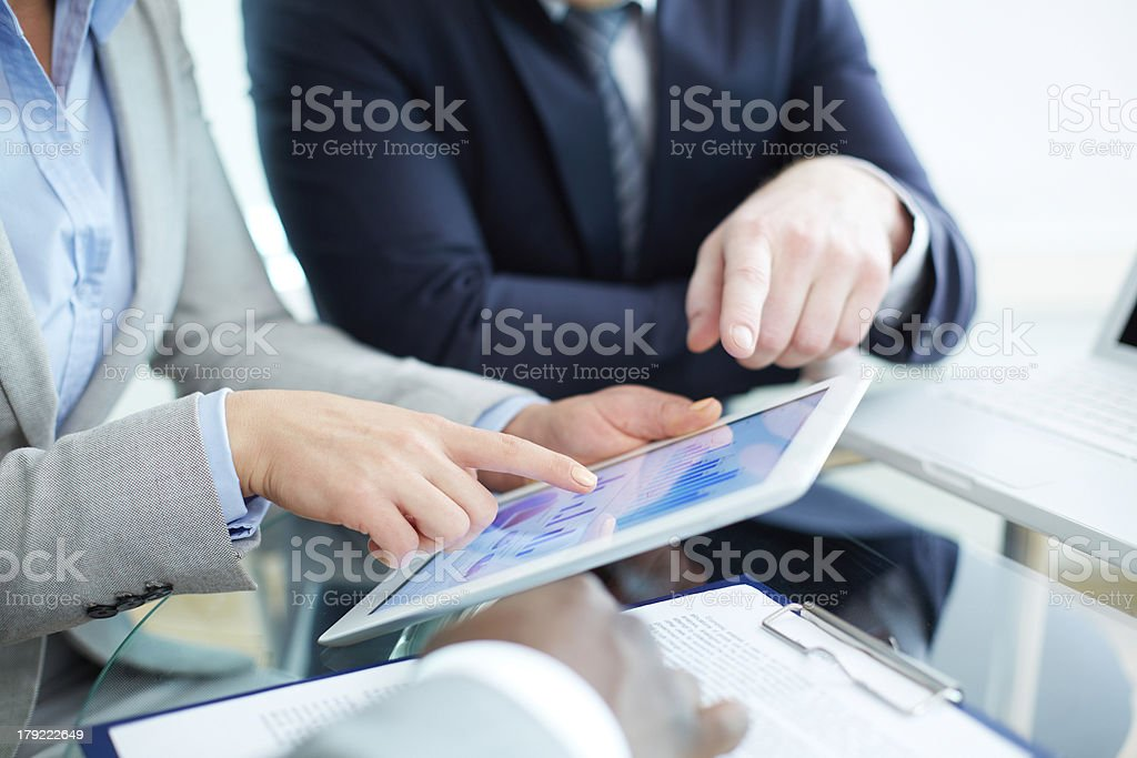 Presenting project Image of human hands during discussion of business document in touchscreen at meeting Business Stock Photo