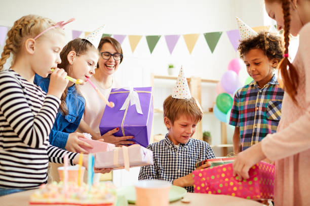 Presents for Birthday Party Portrait of happy  boy opening gifts from friends during Birthday party, copy space group of friends giving gifts to the birthday girl stock pictures, royalty-free photos & images
