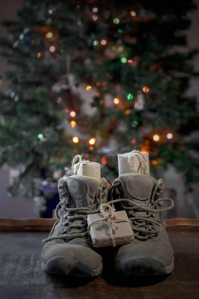 Presents inside hiking boots underneath christmas tree stock photo