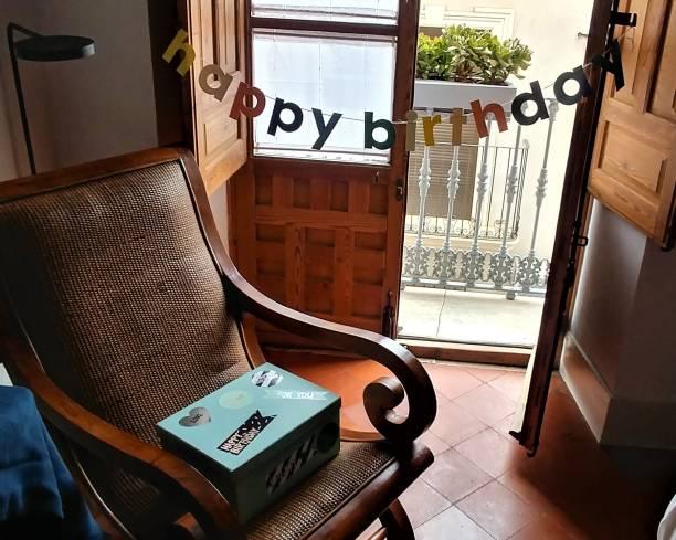 Regalos esperando en una silla y feliz cumpleaños hecho a mano signo - foto de stock