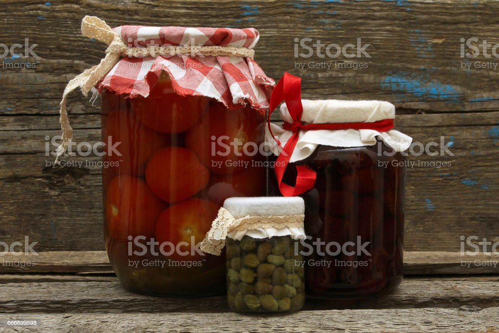 Preserve. Jar with  strawberry jam, pickled tomatoes and capers on wooden background stock photo
