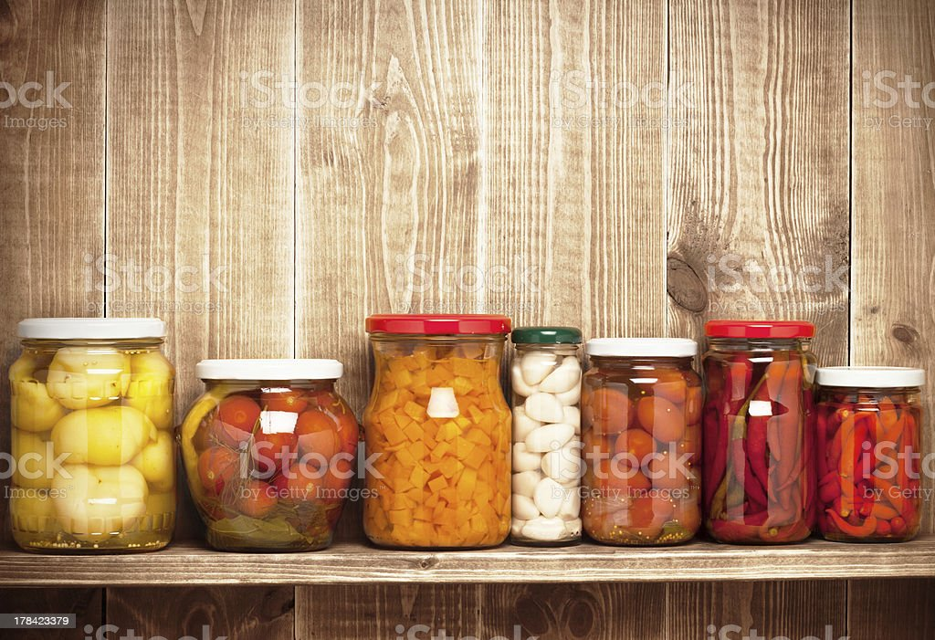 Preserved  autumn vegetables on shelf near a wooden wall stock photo